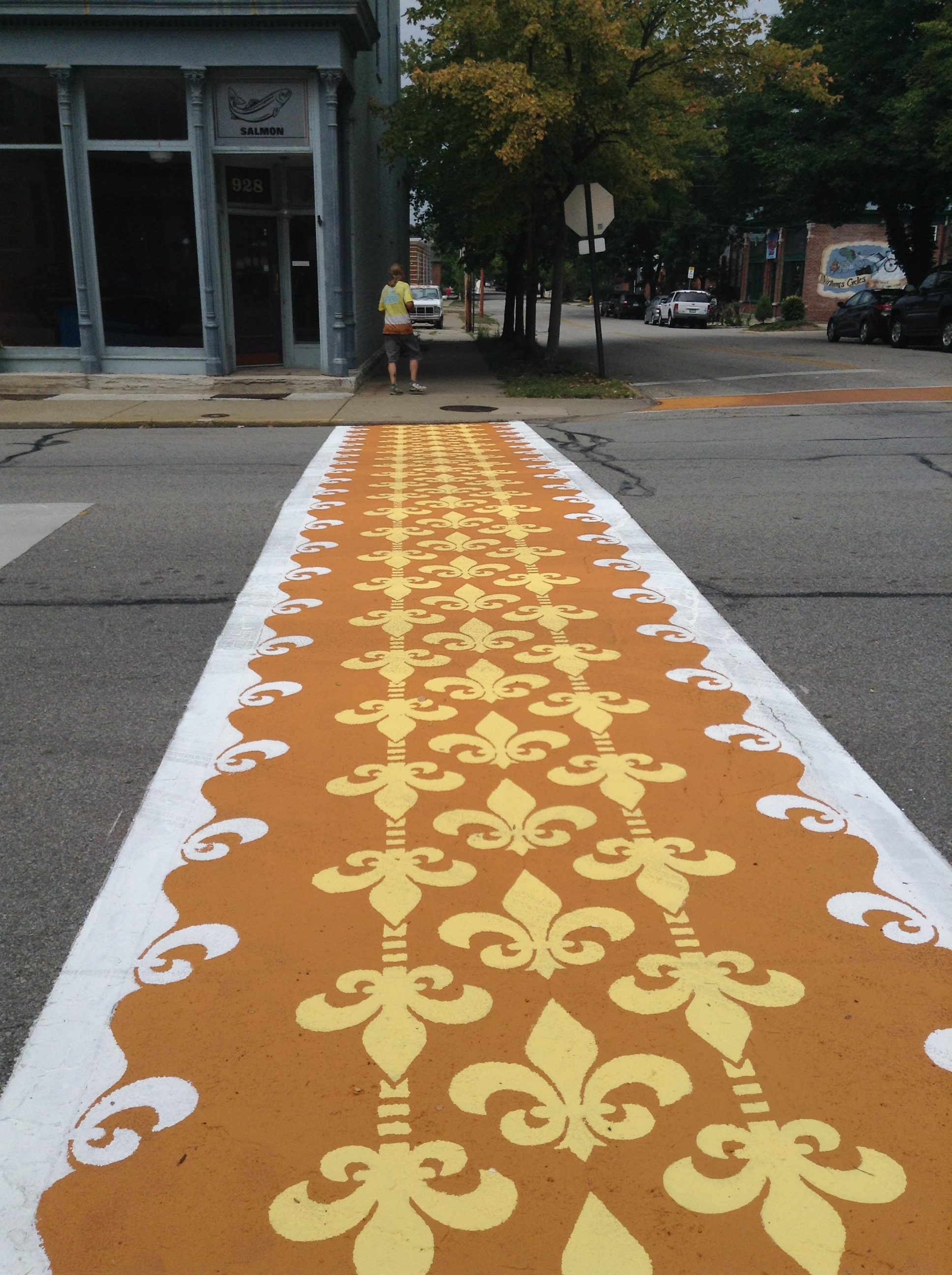 Orange, yellow and white crosswalk pattern made of fleur de lis.